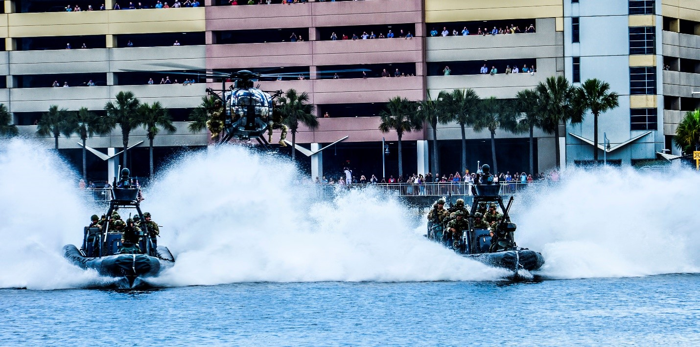 Two rigid-hulled inflatable boats and a MH-6 Little Bird